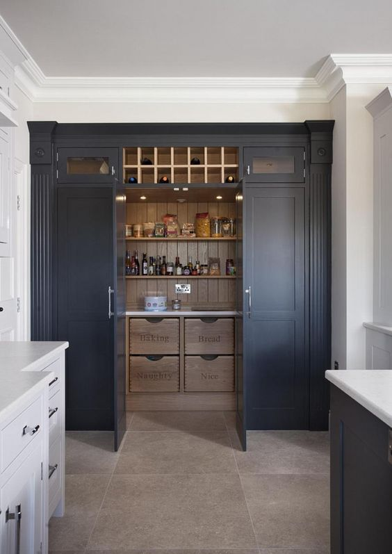 a midnight blue kitchen larger with wooden shelves and drawers used for food and drink storage