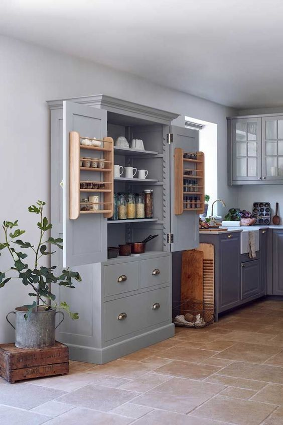 a grey kitchen larger used for tableware and cookware storage and some spices and food