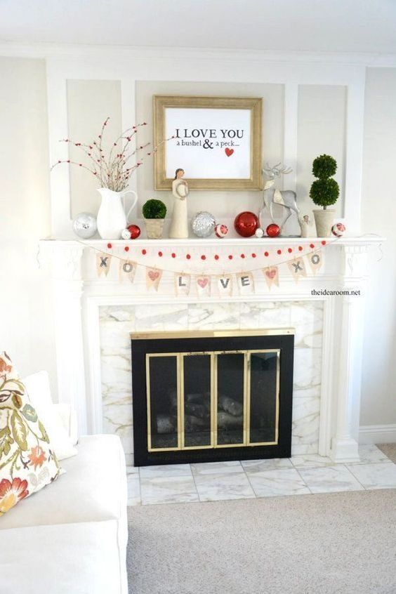 a Valentine fireplace with silver and red ornaments, branches with red hearts, topiaries