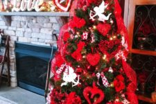 a Valentine tree with white angels, lights, red glitter hearts and red ribbons plus berries