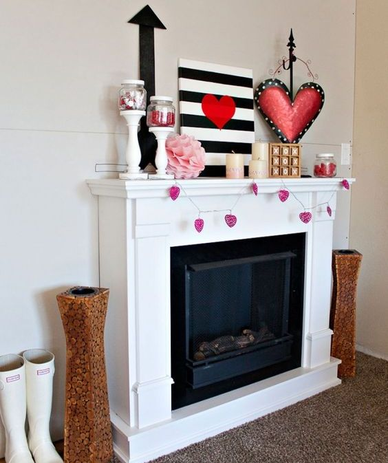 a bold Valentine mantel with a pink heart garland, a striped artworks, paper decor and a large pink heart art