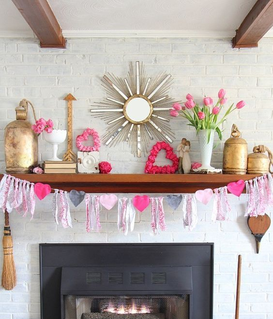 a bright and white Valentine mantel with a heart and tassel garland, pink blooms, pink hearts and gold touches