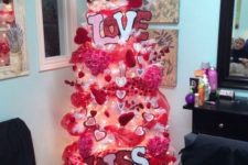 a bright hot pink Valentine tree with lights, fabric blooms, hearts, LOVE letters and hot pink ribbons