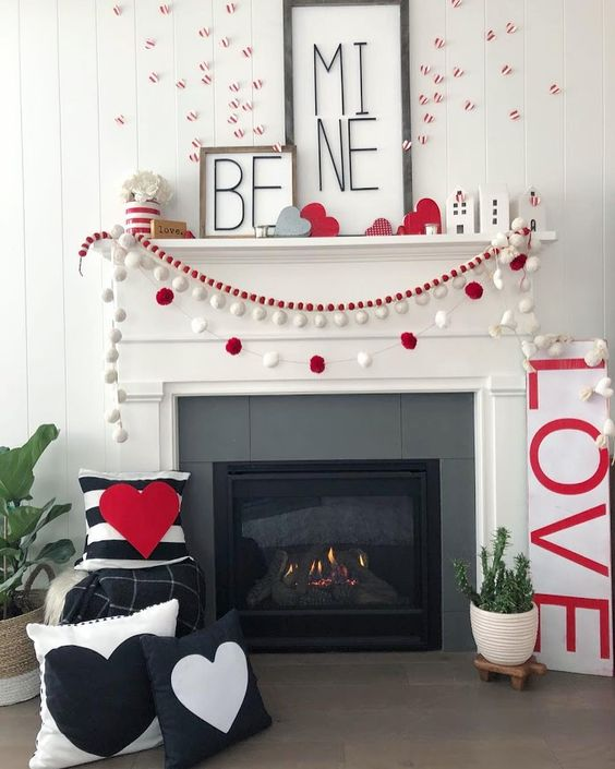 a chic Valentine fireplace with red and white pompoms garlands, heart throws, a couple of signs and red and white decor on the wall