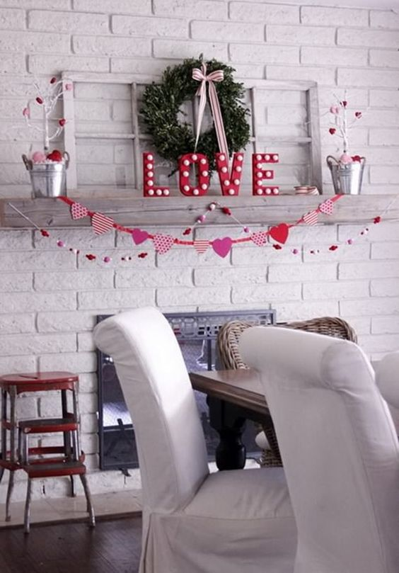 a chic and simple Valentine mantel with marquee letters, white trees with hearts, a greenery wreath and garlands