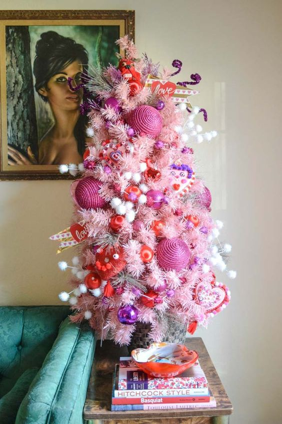 a colorful and whimsy Valentine tree in pink with white pompoms, pink and red ornaments and heart decor