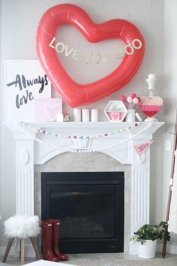 a cool Valentine fireplace with a pompom garland, candles, hearts and a large balloon heart