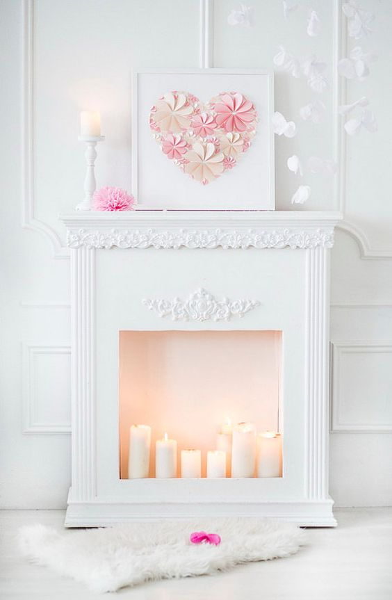 a cute Valentine fireplace with candles, an artwork with a paper heart, candles and white petals in the mid-air