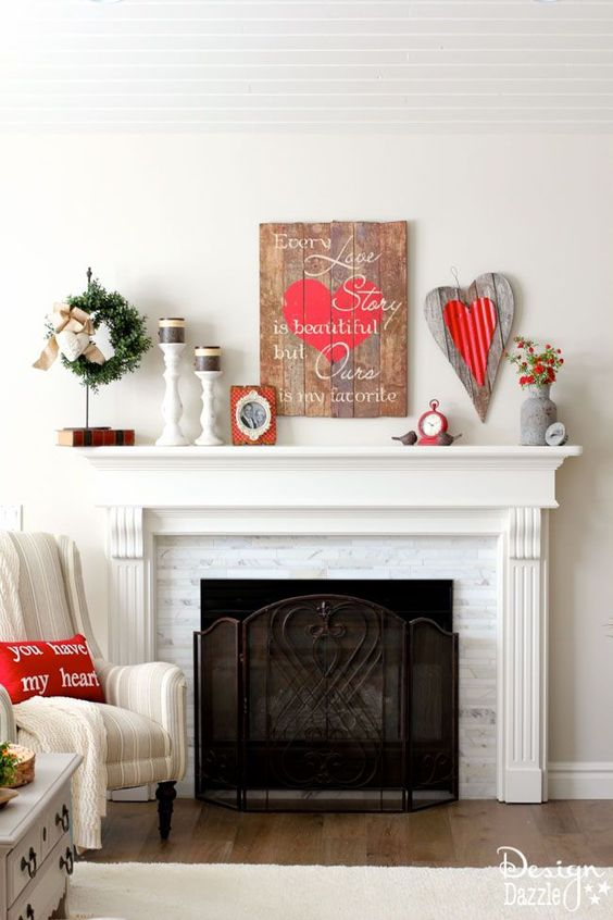 a cute Valentine mantel with a wooden sign, a plaque heart, black candles, red blooms in a churn