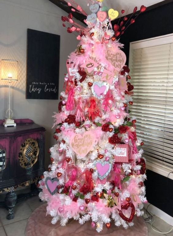 a fancy Valentine tree with pink and red heart ornaments, paper hearts, conversation hearts and lights