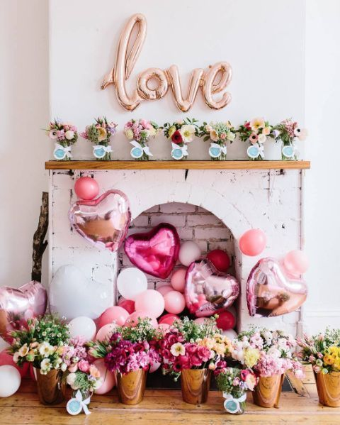 a gorgeous and sassy Valentine fireplace with lots of pink balloons, lush blooms in vases and on the mantel
