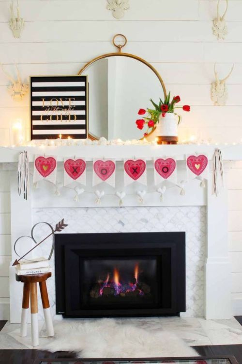 a modern Valentine fireplace with a pink heart garland, candles, pink tulips and a striped sign