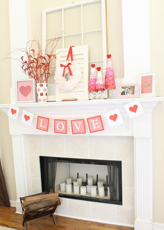 a simple Valentine mantel with red branches, ombre trees, a cool garland and lots of photos