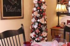a tall tree with snowflakes, hearts and red and white ornaments plus a heart topper for Valentine's Day
