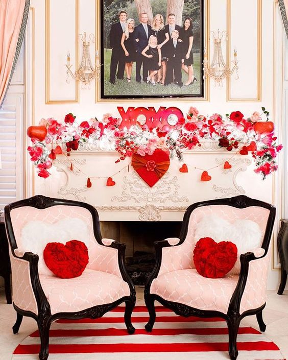 a very lush and formal Valentine fireplace with lots of light, heart and floral garlands, XO letters and heart throws