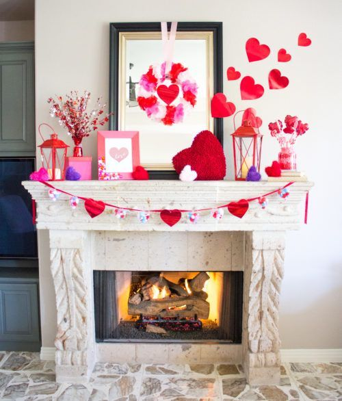 a whimsical Valentine mantel with fluffy colorful hearts, red candle lanterns and red hearts on the wall