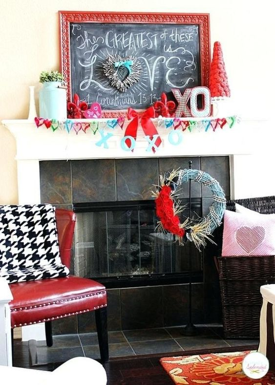 a whimsy Valentine mantel with a colorful felet heart garland, XO letters, a red bloom tree and a chalkboard sign