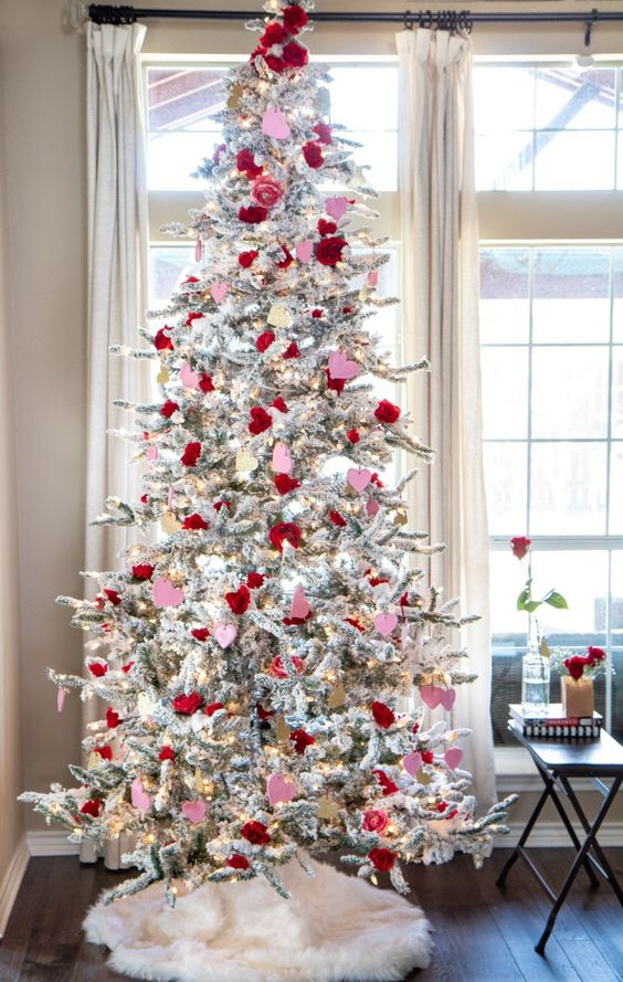 a whimsy snowy Valentine tree with lights, red and pink roses and hearts and some heart ornaments