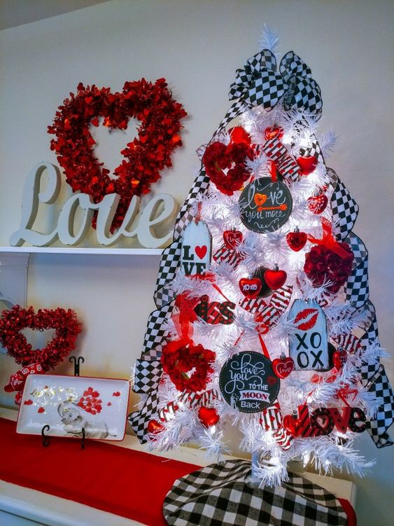 a whimsy tabletop Valentine tree with checked ribbons, lights, red rose wreaths, red heart ornaments and tags