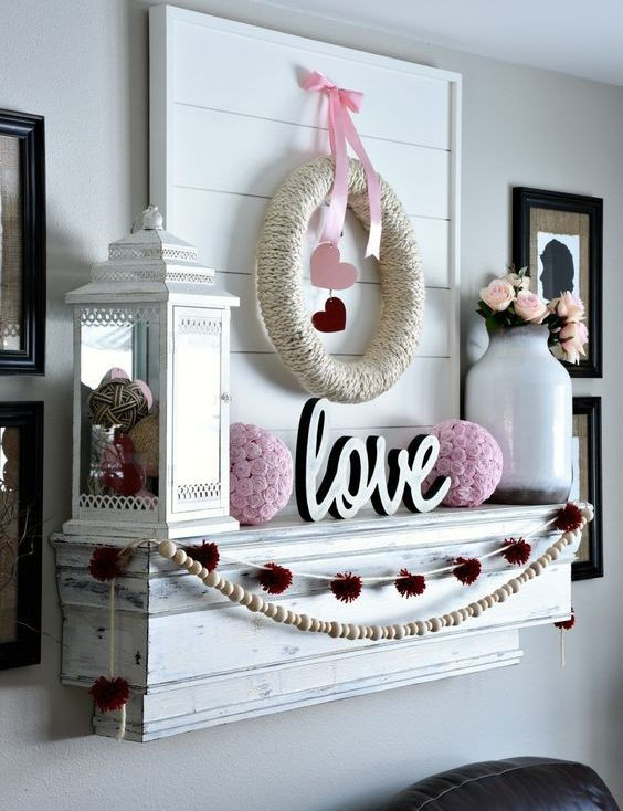 a whitewashed mantel with pink balls, pink blooms, a lantern with balls and pompom and bead garlands