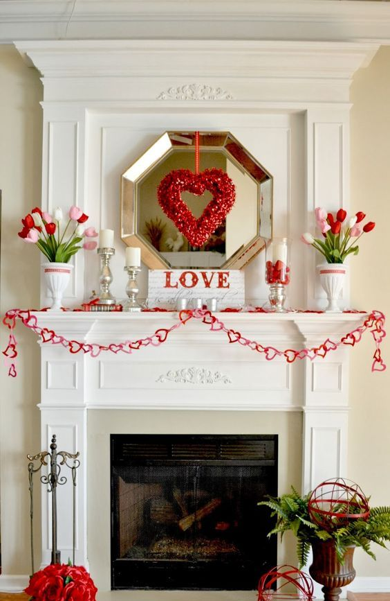 an elegant Valentine fireplace and mantel, with pink and red tulips, a heart wreath and a heart garland