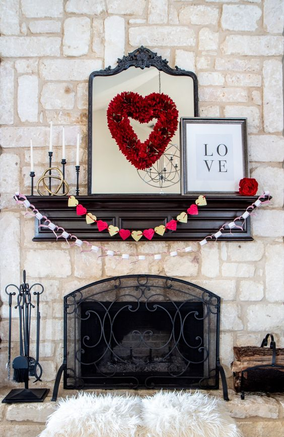 an elegant Valentine mantel with a red heart, paper heart garlands and red blooms
