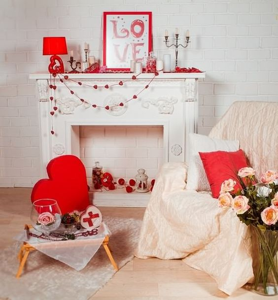 cute and romantic Valentine fireplace styling with heart garlands, candles, a sign, a red lamp and red heart pillows