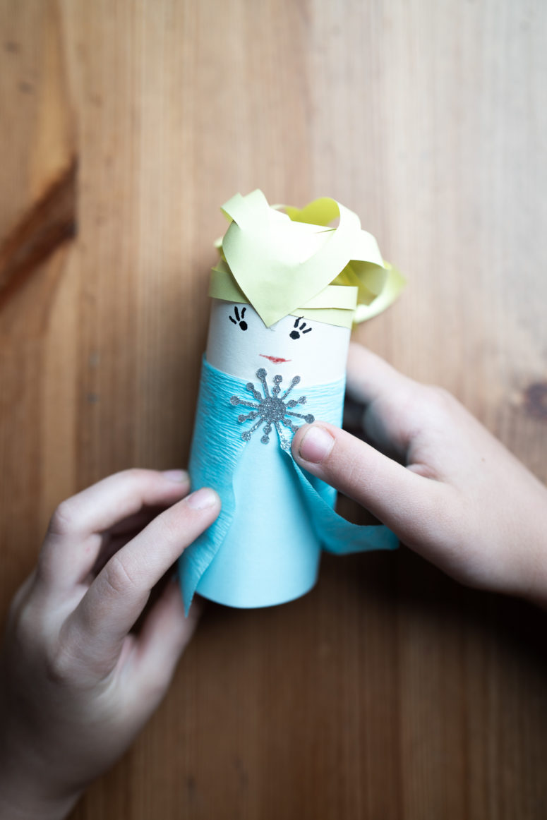 . Cut a rectangle from crepe paper to make a cloak, and from silver paper cut out a snowflake for decoration.