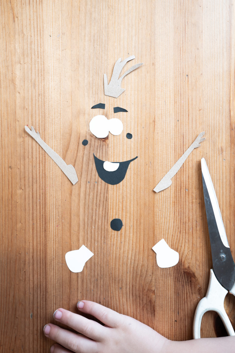 Cut out the remaining parts of the snowman's body: white eyes and a tooth, black eye apples, eyebrows and a mouth. Cut out sticks for arms and hair from brown paper.