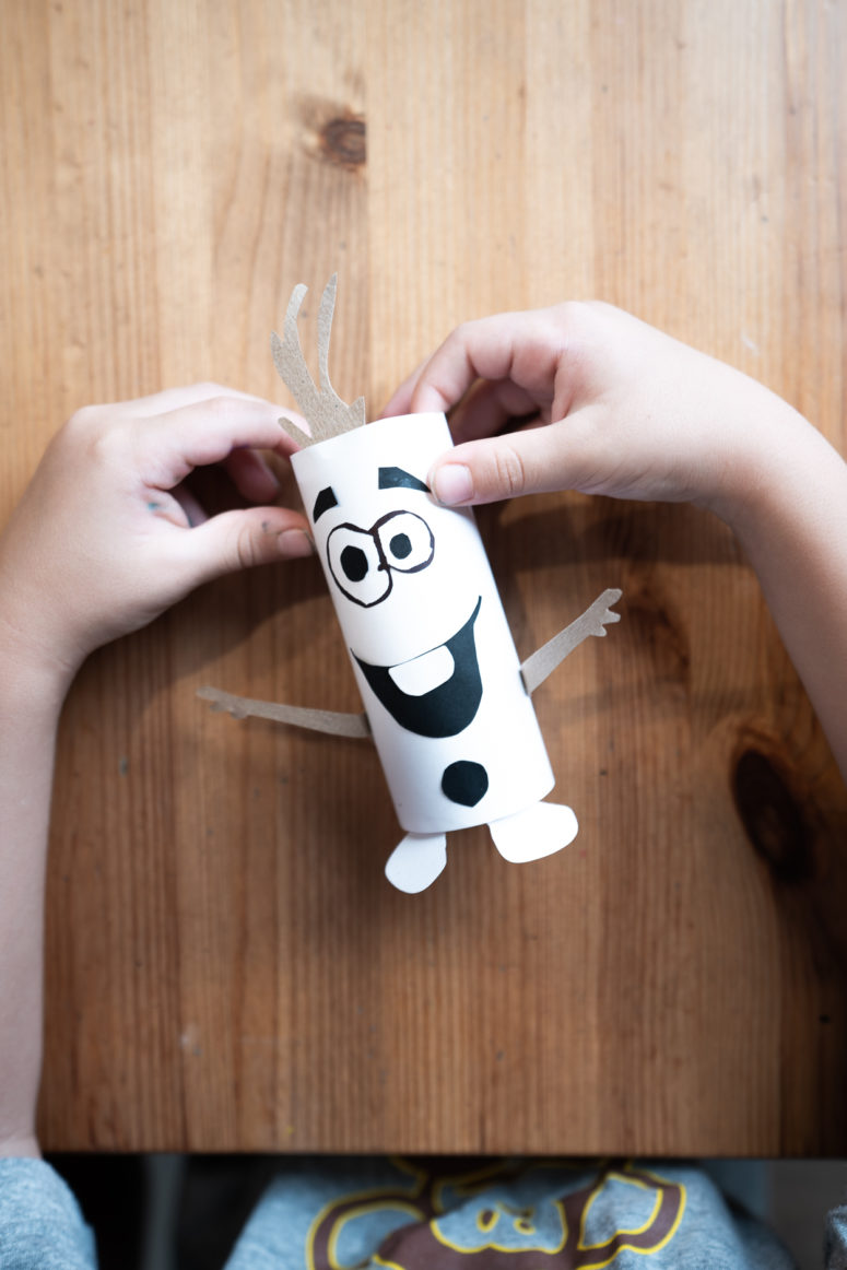 Line up the eyes with a black marker and glue all the parts onto the white paper roll — Olaf's body.