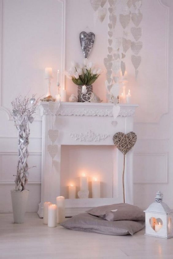 neutral faux fireplace decor with white paper hearts, candles on the mante and inside the fireplace and white tulips