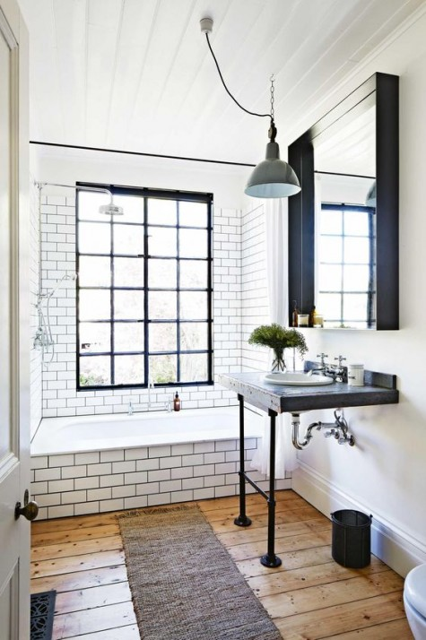an industrial bathroom with white subway tiles, black grout and black accents in the bathroom for some drama