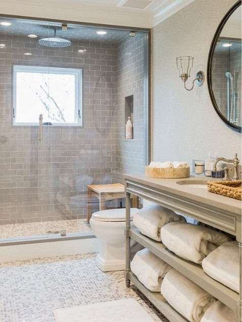 grey tiles with white grout in the shower space make it stand out in the neutral bathroom