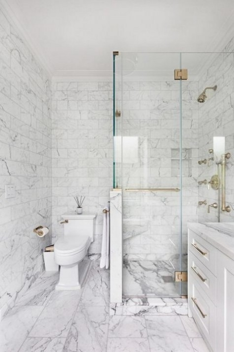white marble tiles on the walls and floor, smaller ones and larger ones on the floor for a timeless bathroom look