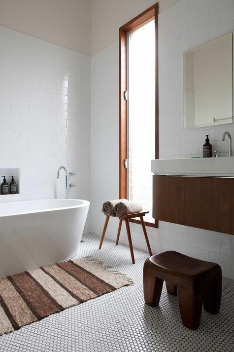 a neutral bathroom with a white penny tile floor and white subway tiles plus rich stained wooden items