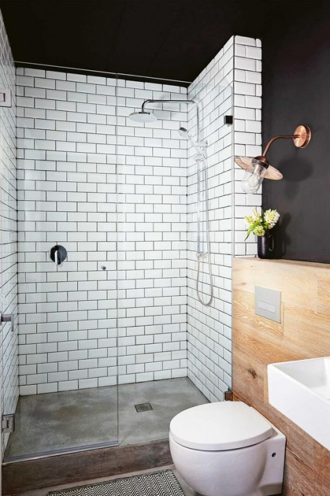 the shower space covered with white subway tiles and black grout plus a black ceiling for a contrast