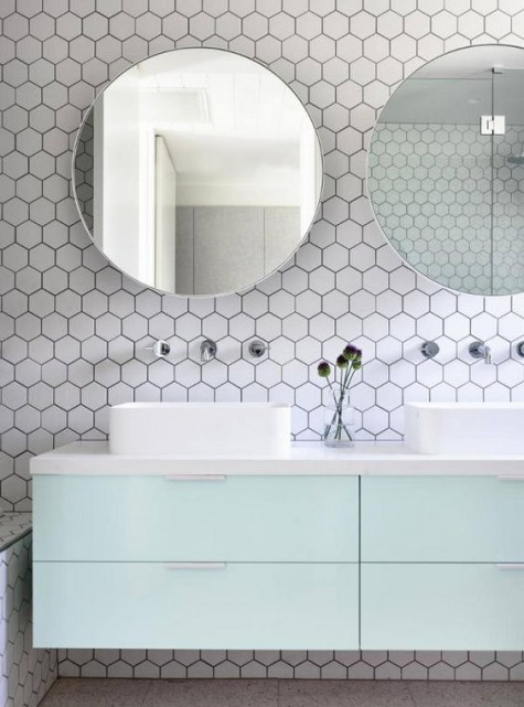 white hex tiles with black grout contrast are done fresh and bold with pastel mint cabinets