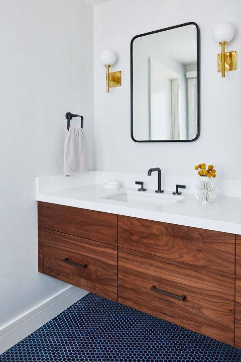 a contemporary bathroom with a navy penny tile floor and white walls for a contrast