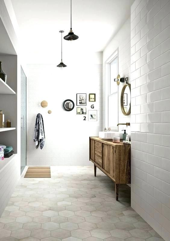 a neutral bathroom with white subway tiles on the walls and neutral marble hex ones on the floor