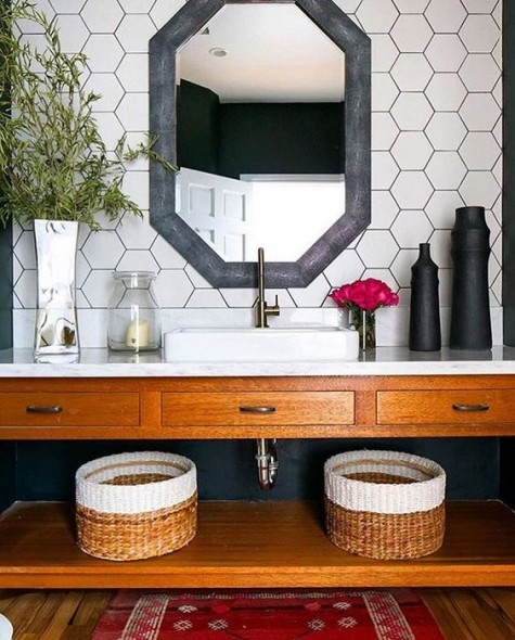 white hex tiles with black grout, a geometric mirror in a grey frame, woven baskets for a chic farmhouse look