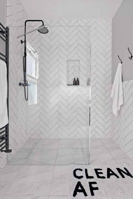 a contemporary bathroom with large scale marble tiles on the floor and herringbone tiles on the walls