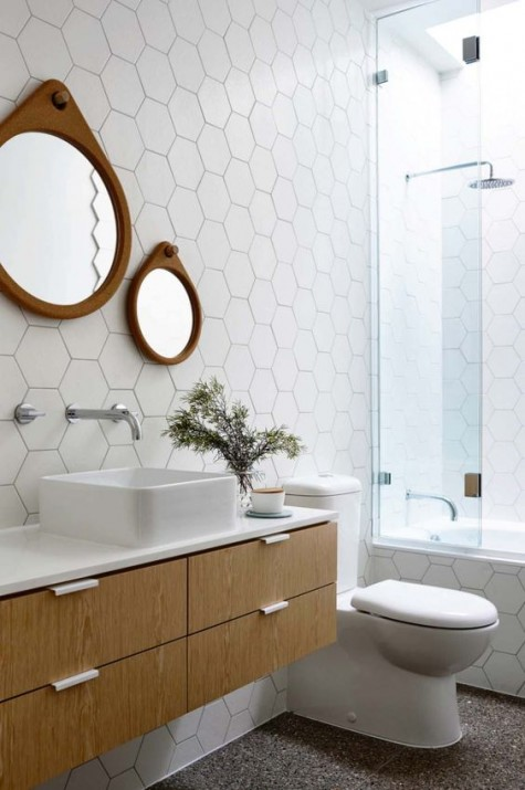 white hex tiles with black grout on the walls, a floating vanity and a duo of mirrors in wooden frames for an interesting look