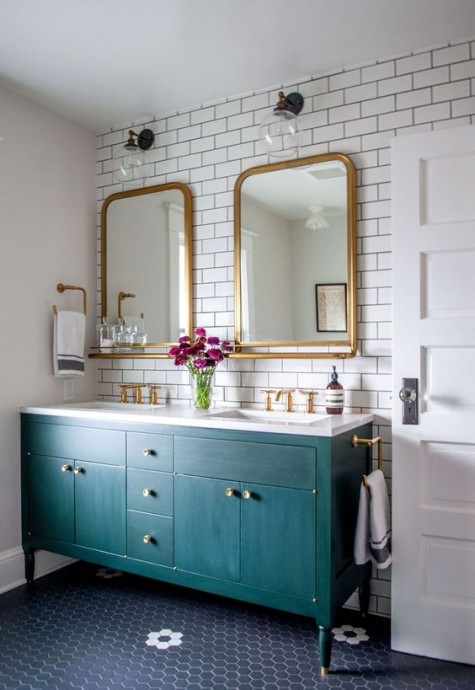 an eye catchy bathroom with white subway tiles, a teal vanity and brass mirrors and other touches for a chic look