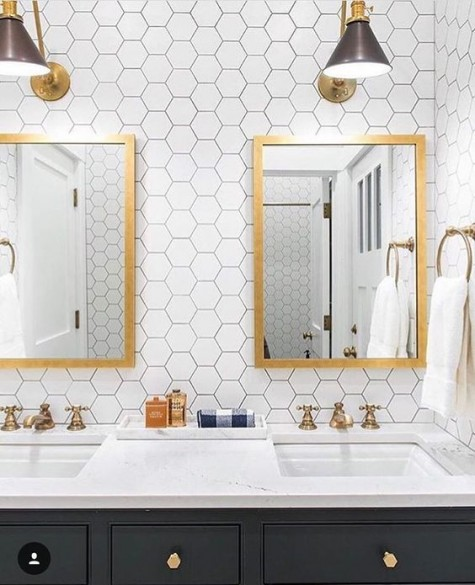 white hex tiles with black grout, gold mirrors, faucets and scaonces make the space elegant and stylish