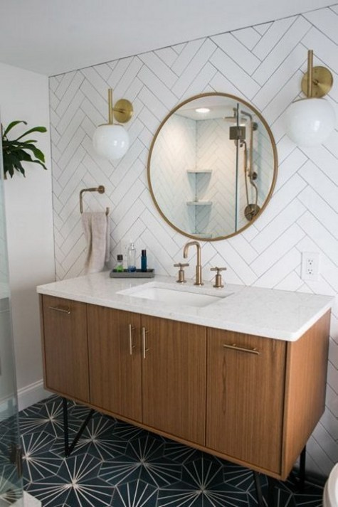 a green and gold art deco tile floor and a white herringbone tile wall that contrast each other and make a bold cohesive look