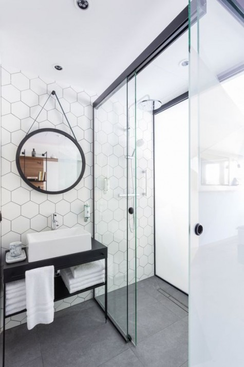 white hexagon tiles on the accent wall and grey tiles on the floor create a chic and stylish combo for a bathroom