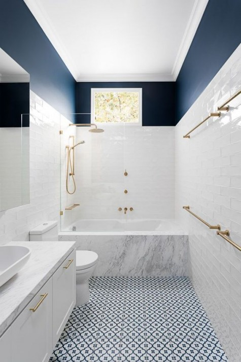 a mosaic blue and white tile floor, white tiles on the walls and a navy top for a contrast