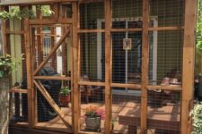 11 a cat enclosure with wooden furniture, potted blooms and greenery and some more furniture for comfortable staying