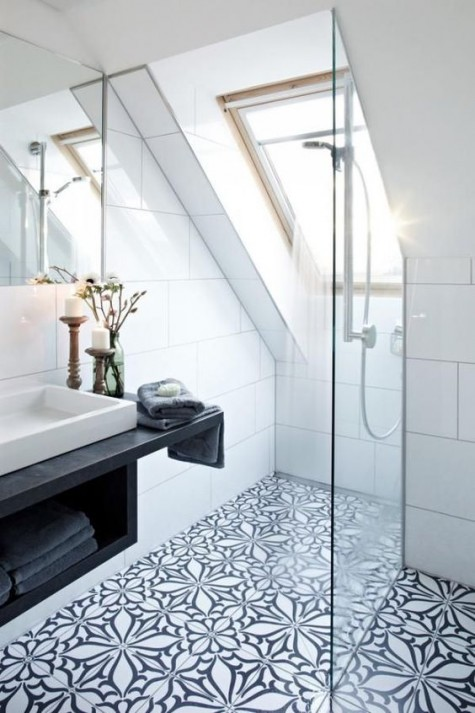 a small attic bathroom with a navy and blue mosaic tile floor and white tile walls plus a black floating vanity