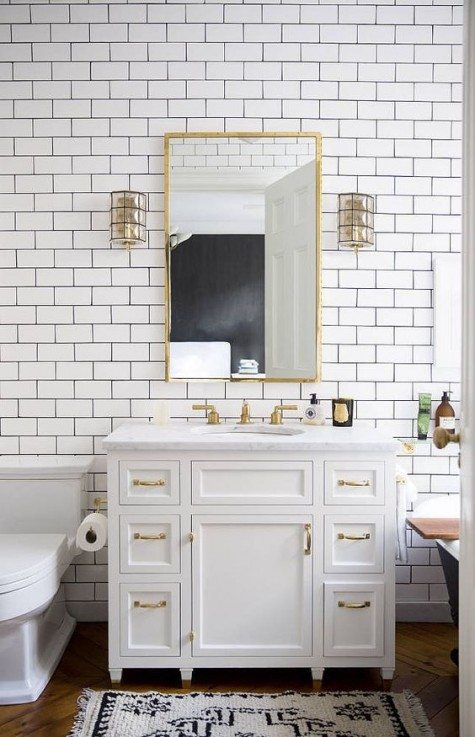white subway tiles with black grout look chic and brass details add a refined and chic touch to the space